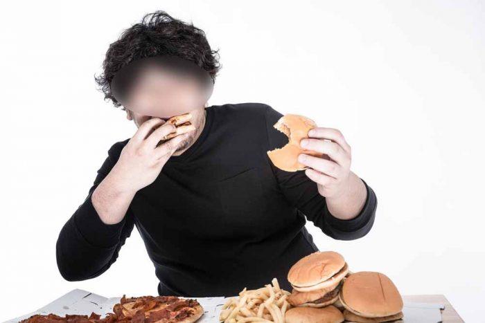 食べ過ぎている男性の写真